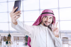 Arabic tourist taking selfie in the airport. Portrait of Arabian tourist using a smartphone to take selfie picture in the airport Royalty Free Stock Photography