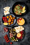 Arabic traditional cuisine. Middle Eastern meze platter with pita, olives, hummus, stuffed dolma, labneh cheese balls, falafel. Royalty Free Stock Images