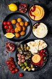 Arabic traditional cuisine. Middle Eastern meze platter with pita, olives, hummus, stuffed dolma, labneh cheese balls, falafel. Royalty Free Stock Photo