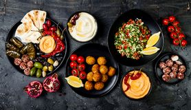 Arabic traditional cuisine. Middle Eastern meze platter with pita, olives, hummus, stuffed dolma, labneh cheese balls in spices. stock photo