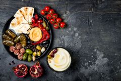 Arabic traditional cuisine. Middle Eastern meze platter with pita, olives, hummus, stuffed dolma, labneh cheese balls in spices. Mediterranean appetizer party stock photos