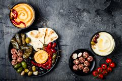 Arabic traditional cuisine. Middle Eastern meze platter with pita, olives, hummus, stuffed dolma, labneh cheese balls in spices. Stock Image