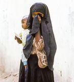 Arabic unknown mother carries her baby. HADHRAMAUT, YEMEN - MAY, 15: arabic unknown mother carries her baby in a  wraparound garment on May 15, 1993 in Stock Photography
