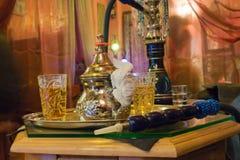 Arabic water pipe at Granada. Arabic water pipe with tea set in beautiful arabic decor at Granada downtown, Spain Royalty Free Stock Photo