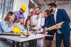 Arabic and western business people speaking about investments. In office Royalty Free Stock Photos
