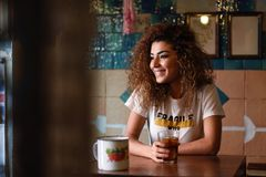 Arabic woman in a beautiful bar looking through the window. Young arabic smiling woman with black curly hairstyle sitting in a beautiful bar with vintage Stock Image