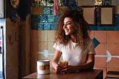 Arabic woman in a beautiful bar looking through the window. Young arabic smiling woman with black curly hairstyle sitting in a beautiful bar with vintage Stock Photo