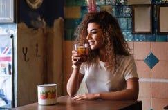 Arabic woman in a beautiful bar looking through the window. Young arabic woman with thoughtful gesture sitting in a beautiful bar with vintage decoration. Arab Stock Photo