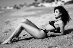Arabic woman with beautiful body in bikini lying on the beach sa. Young arabic woman with beautiful body in swimwear lying on the beach sand. Brunette female Stock Images