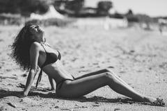 Arabic woman with beautiful body in bikini lying on the beach sa. Young arabic woman with beautiful body in swimwear lying on the beach sand. Smiling female with stock photos
