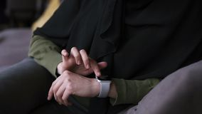 Arabic woman in black hijab sitting in modern cafe alone and using her smart watches, swipe the data with finger. Slow. Motion. Close up stock video footage