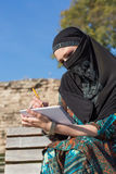 Arabic Woman drawing Sketch in Paper Notepad with Pencil. Arabic Woman drawing Sketch of Ancient Ruin in Paper Notepad with Pencil sitting on wooden bench Stock Photos