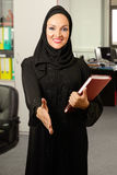 Arabic woman, greeting a person inside office. Arabic woman, greeting a person inside the office Royalty Free Stock Photo