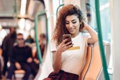 Arabic woman inside subway train looking at her smartphone. Arabic woman inside subway train looking at her smart phone. Arab girl in casual clothes Royalty Free Stock Image