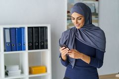 Arabic woman looking at phone stock photos