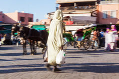 Arabic woman in Marrakesh in motion blur. Arabic woman with shopping bag on a square in Marrakesh in motion blur Stock Photography