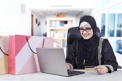 Arabic woman with notebook and credit card. Picture of Arabic young woman shopping online at home with notebook and credit card Royalty Free Stock Images