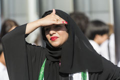 Arabic woman obscures the sun. Beautiful arabic woman wearing hijab obscures the sun with her hand. Dubai, UAE, United Arab Emirates Stock Image