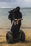 An arabic woman is riding a segway on a beach. An arabic woman is riding a two wheeled stand up transportation device on a beach while wearing traditional whole Stock Photos