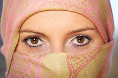 Arabic woman with scarf. A portrait of an arabic woman face hidden behind a beautiful scarf Stock Photography