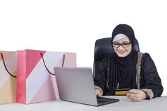 Arabic woman shopping online with notebook. Arabic young woman using a laptop computer and credit card for shopping online with shopping bags on desk Royalty Free Stock Images