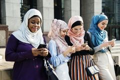 Arabic woman standing and using mobile. Arabic women standing and using mobile together outdoors under the sun Stock Image