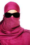 Arabic woman in sunglasses. A portrait of an arabic woman face hidden behind a purple scarf Royalty Free Stock Photos