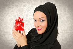 Arabic woman, traditional dressed holding present Stock Image