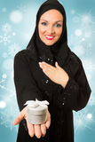 Arabic woman, traditional dressed holding present. Model dressed in traditional Arabic style, holding present box in her hand Stock Images