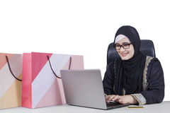 Arabic woman using laptop for shopping online. Picture of Arabic young woman using a notebook computer for shopping online with shopping bags on desk Stock Images