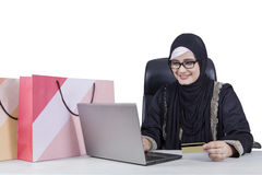 Arabic woman with veil shopping online. Beautiful Arabic woman using credit card and laptop for shopping online with shopping bags on the table Royalty Free Stock Image