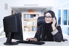 Arabic woman working at home. Arabic businesswoman wearing headscarf talking on the cellphone while working at home Stock Photos
