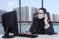 Arabic woman working near the window. Arabian businesswoman working in the office with a computer near the window while talking on the cellphone Stock Images
