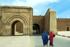 Arabic women with hijab in front of old city gate, Morocco. Two arabic styled women in front of an city wall gate Royalty Free Stock Photo