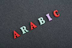 ARABIC word on black board background composed from colorful abc alphabet block wooden letters, copy space for ad text. Learning english concept stock photos