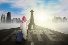 Arabic worker on the employment rate road. Middle eastern businessman carrying bag and walks on the road with a text of employment rate and upward arrow Royalty Free Stock Image
