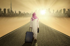Arabic worker with luggage walks on the road. Image of Arabic businessman walking on the road while carrying luggage and wearing islamic clothes Stock Photography