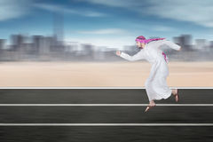 Arabic worker running on the highway. Rear view of Arabic young businessman running on the highway while wearing islamic clothes Stock Image