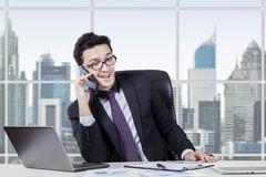 Arabic worker speaking on the cellphone. Photo of Arabic young entrepreneur working in the office while speaking on the cellphone with a laptop on desk Stock Photos