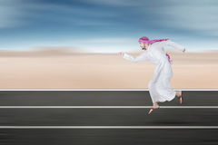 Arabic young businessman running on street. Portrait of Arabic young entrepreneur running on the street while wearing islamic clothes Stock Photo