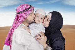 Arabic young couple kiss their son. Picture of Arabic young couple wearing islamic clothes and kiss their son on the desert Royalty Free Stock Photo