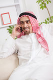 Arabic young man with phone on sofa. Portrait of young Arab having phone conversation in living room Stock Image