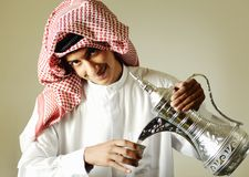 Arabic young man pouring a coffee. Arabic young man pouring a traditional coffee Royalty Free Stock Image