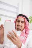 Arabic young man with tablet on sofa. Portrait of young Arab using digital tablet on sofa Royalty Free Stock Photos
