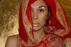 Arabic young woman. Gold makeup. Red clothes. Portrait of beautiful arabic young woman with gold makeup. Red clothes. Shawl with ornament. Gold ring with Royalty Free Stock Photo