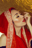 Arabic young woman. Gold makeup. Red clothes. Portrait of beautiful arabic young woman with gold makeup. Red clothes. Shawl with ornament. Gold ring with Royalty Free Stock Image
