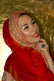 Arabic young woman. Gold makeup. Red clothes. Portrait of laughing beautiful arabic young woman with gold makeup. Red clothes. Shawl with ornament. Gold ring Royalty Free Stock Photos