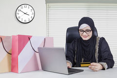 Arabic young worker shopping online. Arabic female worker using credit card and laptop for shopping online in the office Stock Photos