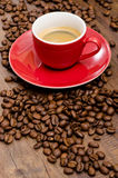Arabica beans and red espresso mug. In vertical format Royalty Free Stock Image