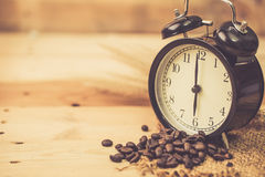 Arabica coffee bean with vintage clock. On wood background, wake up morning time with coffee concept Stock Photography